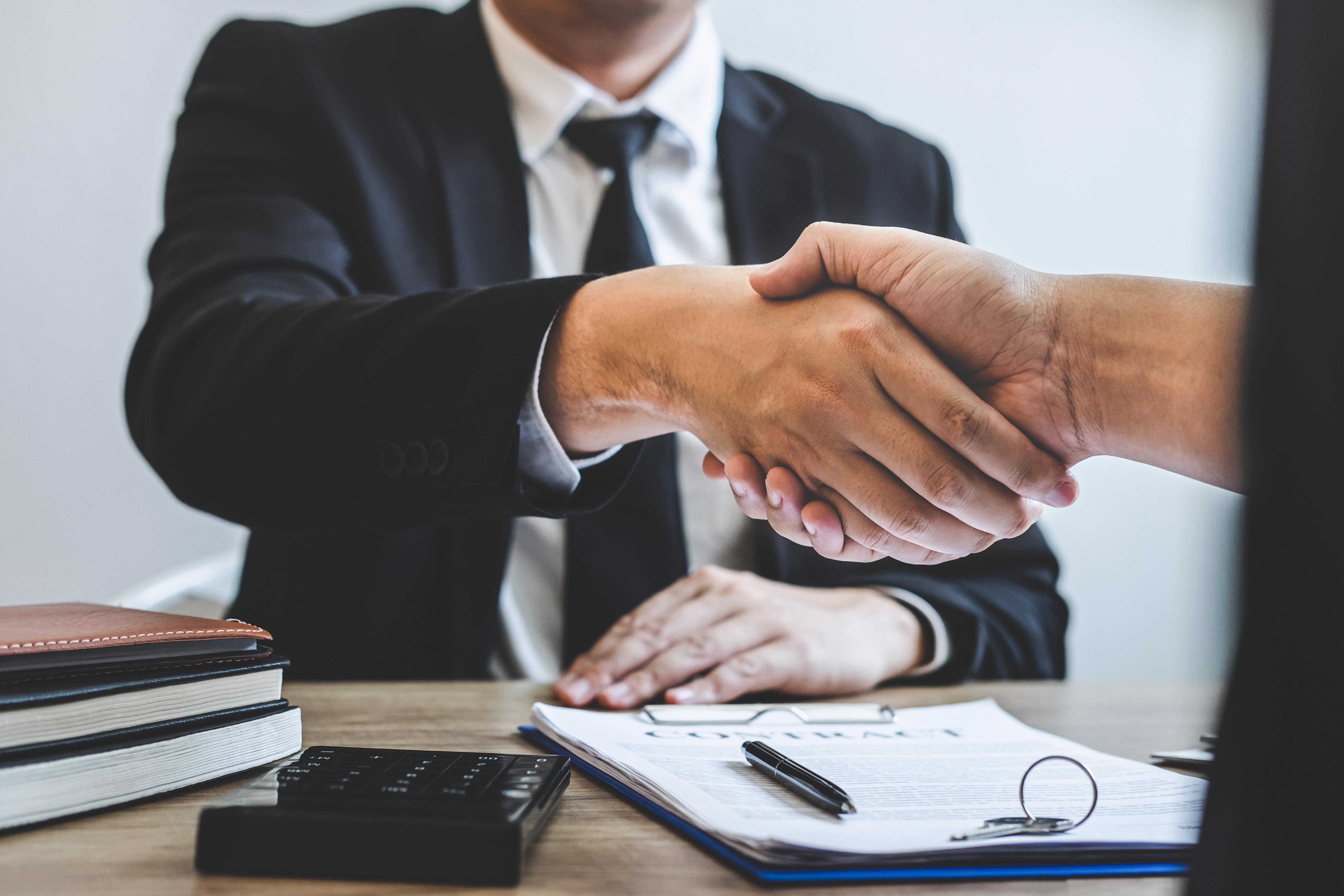 two gentlemen shaking hands after dealing.